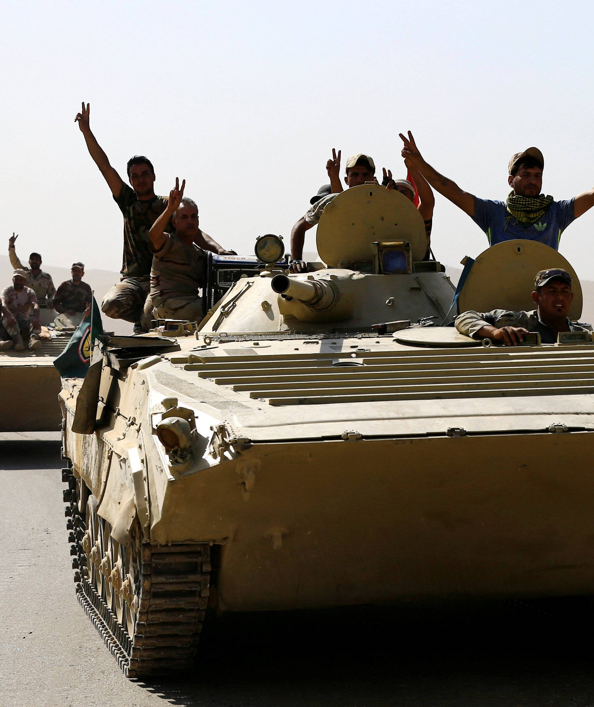 Members of Iraqi Army ride a military vehicle during the war between Iraqi army and Shi'ite Popular Mobilization Forces (PMF) against the Islamic State militants in al-'Ayadiya, northwest of Tal Afar