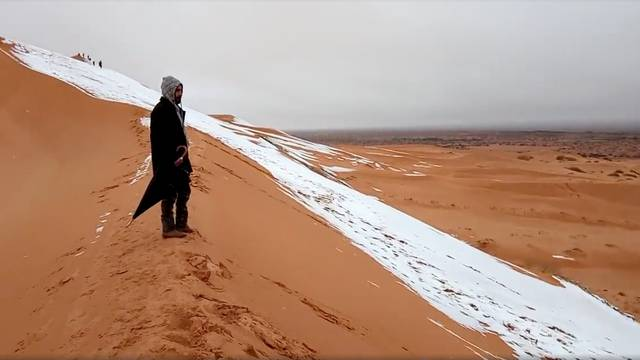 A man looks at at a snow-covered slope in the Sahara, Ain Sefra