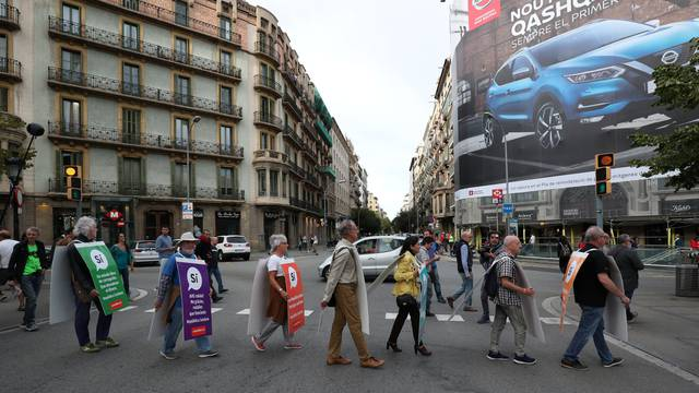 Catalan pro-independence supporters march while they distribute leaflets for the referendum on October 1 by Rambla de Catalunya in Barcelona