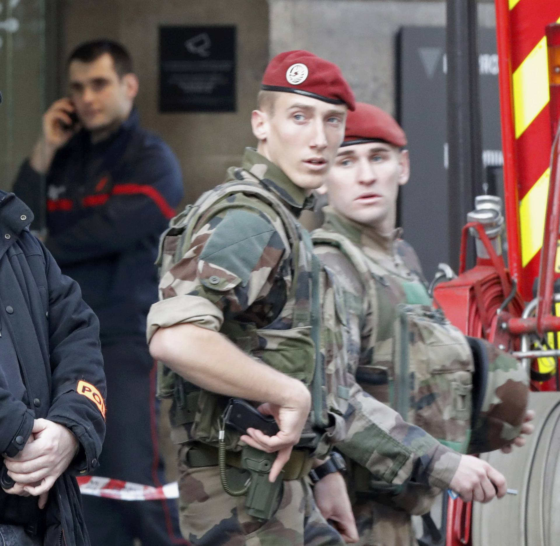 French police, soldiers and firefighters are seen in front of the street entrance of the Carrousel du Louvre in Paris