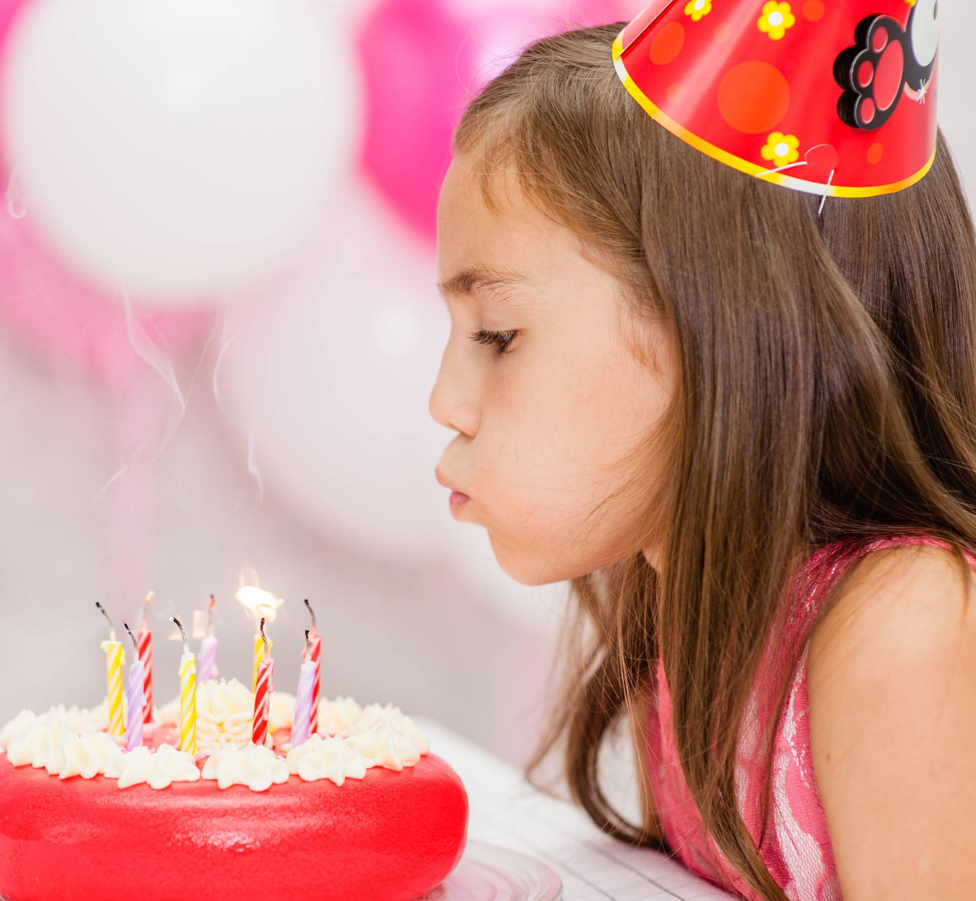Cute girl celebrating his birthday and blowing candles on cake