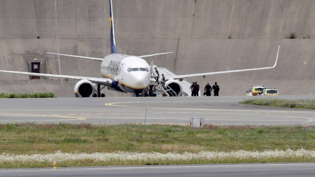 Police officers are seen near a Ryanair plane after it received a bomb threat in Oslo
