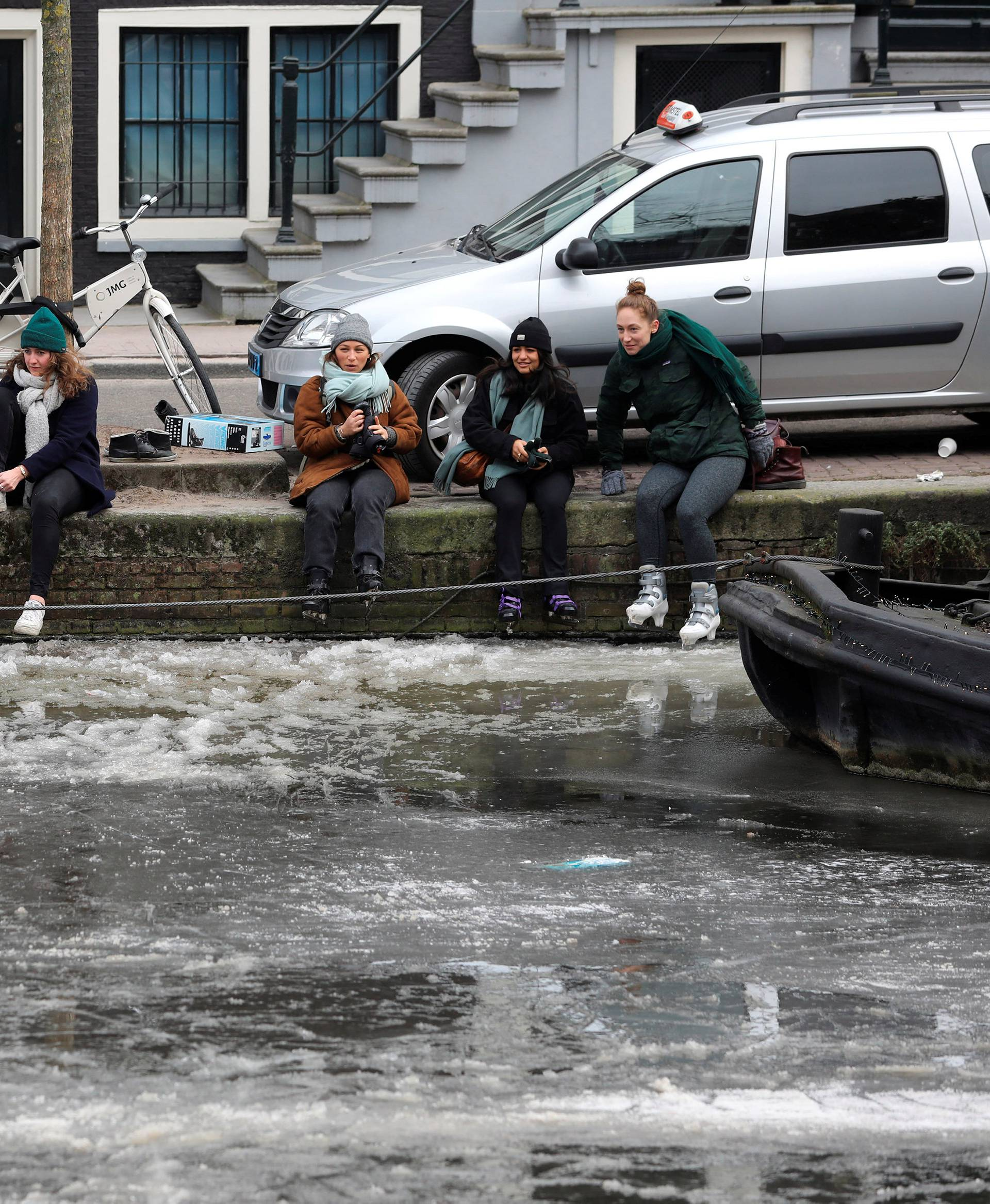 Ice skaters get ready to skate on frozen canal during icy weather in Amsterdam