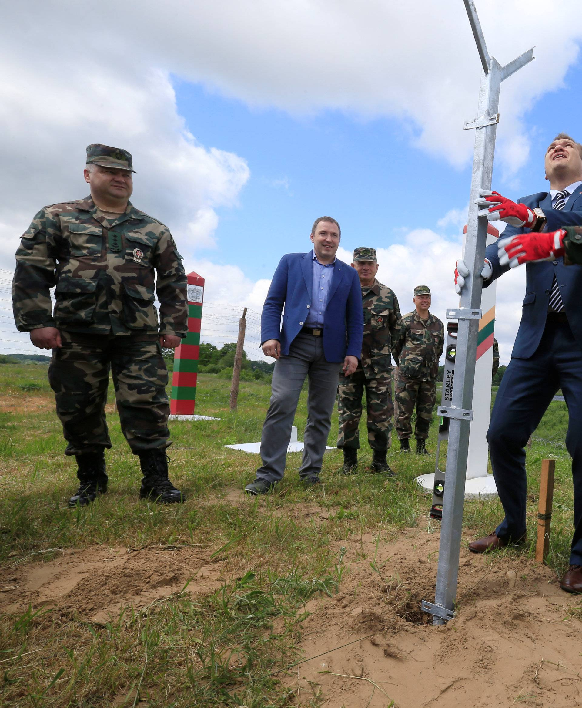 Commander of Lithuanian state border guard Pozela and Interior Minister Misiunas install the first pole for the fence near Sudargas border crossing point in Ramoniskiai