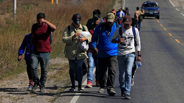 Hondurans, part of a new caravan of migrants travelling towards the United States, walk along a road in Cucuyagua