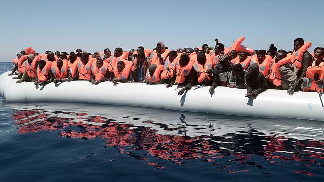 A plastic raft overcrowded with migrants is seen drifting during a search and rescue operation by rescue ship Aquarius, operated by SOS Mediterranean and Doctors without Borders