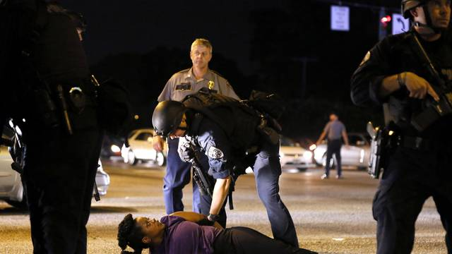 A woman protesting the shooting death of Alton Sterling is detained by law enforcement near the headquarters of the Baton Rouge Police Department in Baton Rouge, Louisiana