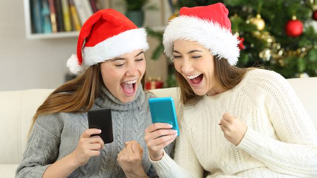 Excited friends watching phone content on christmas