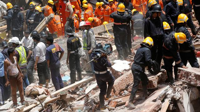 A firefighter arrives with a jack-hammer during a search for survivors at the site of a collapsed building in Mumbai
