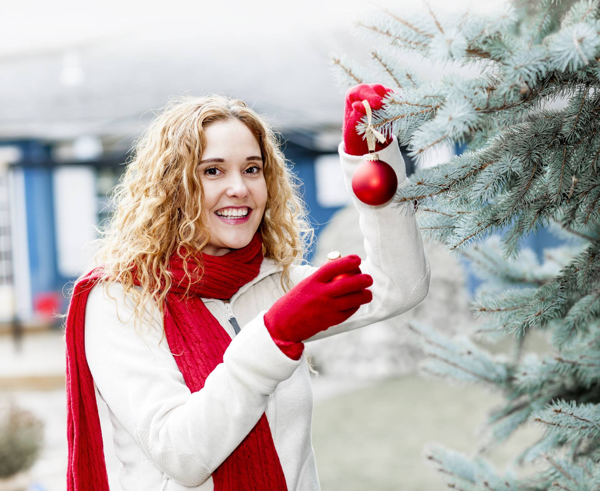Woman decorating Christmas tree outside
