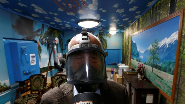 Seiichiro Nishimoto, CEO of Shelter Co., poses wearing a gas mask at a model room for the company's nuclear shelters in the basement of his house in Osaka