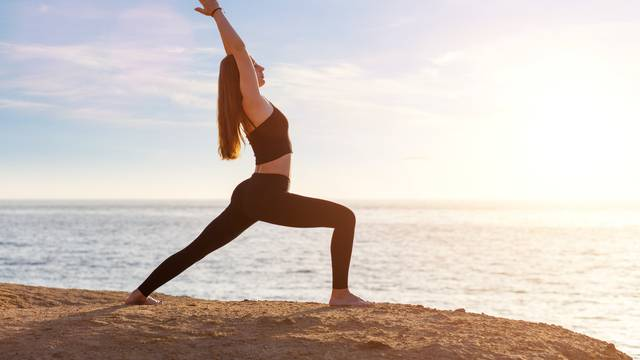 Young woman practicing yoga asana pose in the morning at the sea