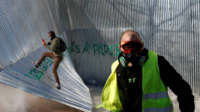 """Protester wearing a yellow vest walks in front of demolished metal fencing during a demonstration by the """"yellow vests"""" movement in Paris"""