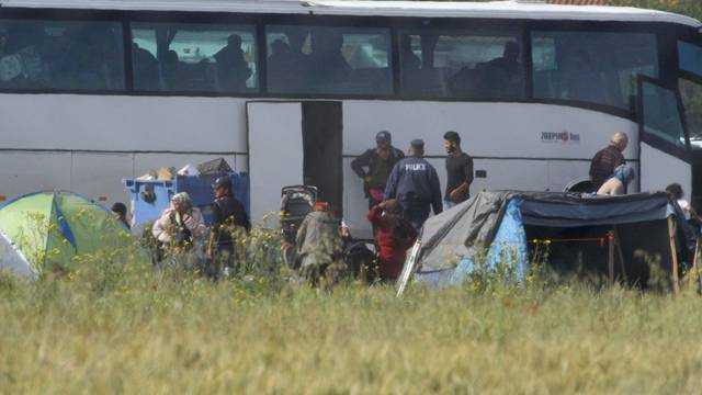 Refugees and migrants are transferred by buses during police operation to evacuate makeshift camp nearIdomeni