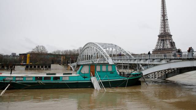 Houseboats are moored near the Eiffel Tower as high waters cover the banks of the Seine River in Paris