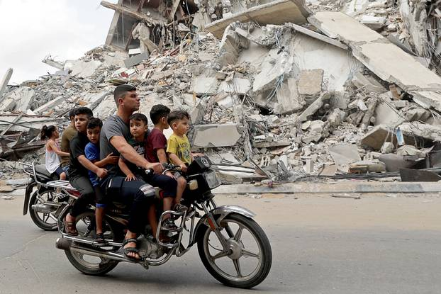 Palestinians ride a motorcycle past the site of an Israeli air strike in Gaza