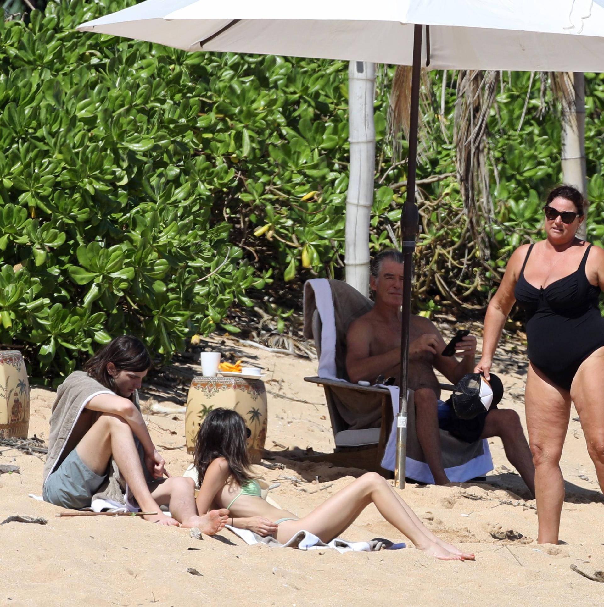 EXCLUSIVE: *NO WEB UNTIL 1530 EST 22ND MAR* Pierce Brosnan hits the beach in Hawaii with his wife Keely Shaye Smith and son Dylan, The former 007 star took a dip in the ocean before relaxing with the family under a umbrella on the beach.
