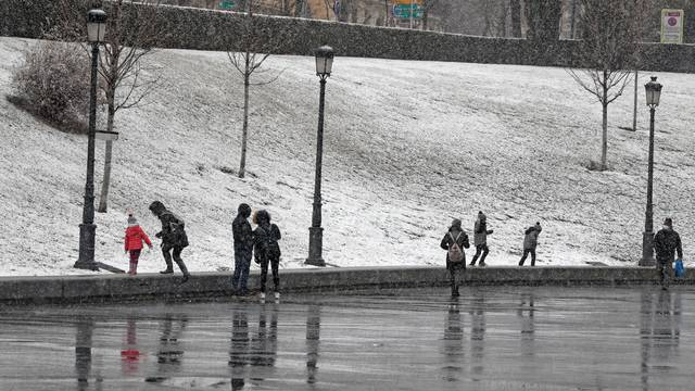 People stand outside the Prado Museum during a snowfall in Madrid