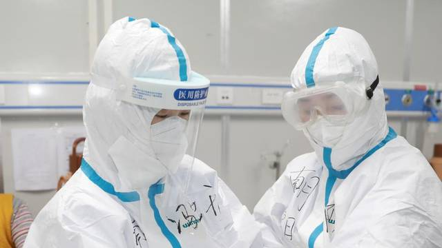 Medical worker writes down a patient's dietary information on a colleague's protective suit inside Leishenshan hospital in Wuhan