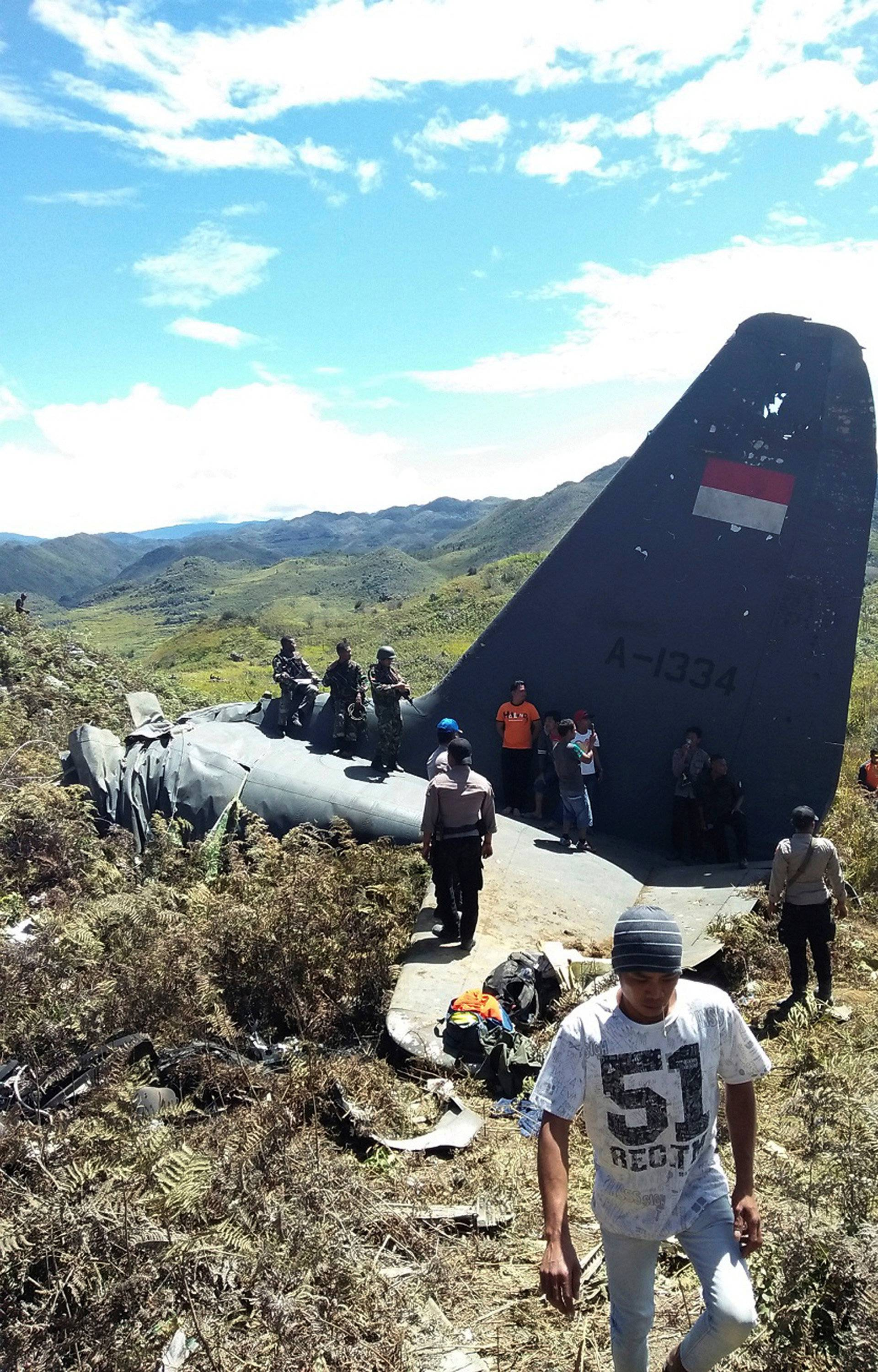 Rescue teams and locals are seen at the crash site of Indonesian air force transport plane which killed all 13 people aboard, on Mount Lisuwa, near Wamena in the remote region of Papua, Indonesia