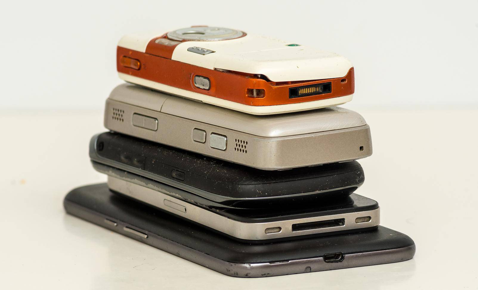 smartphones (used and broken) on white table