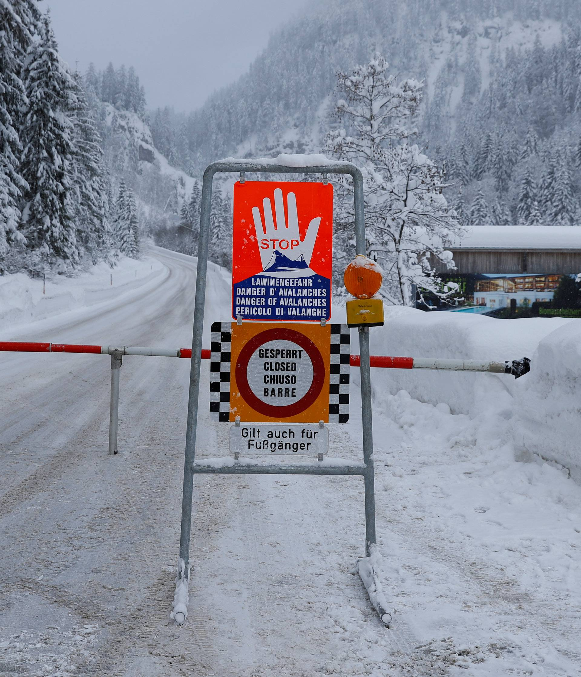 A sign is seen on a closed road after heavy snowfall near Obertauern