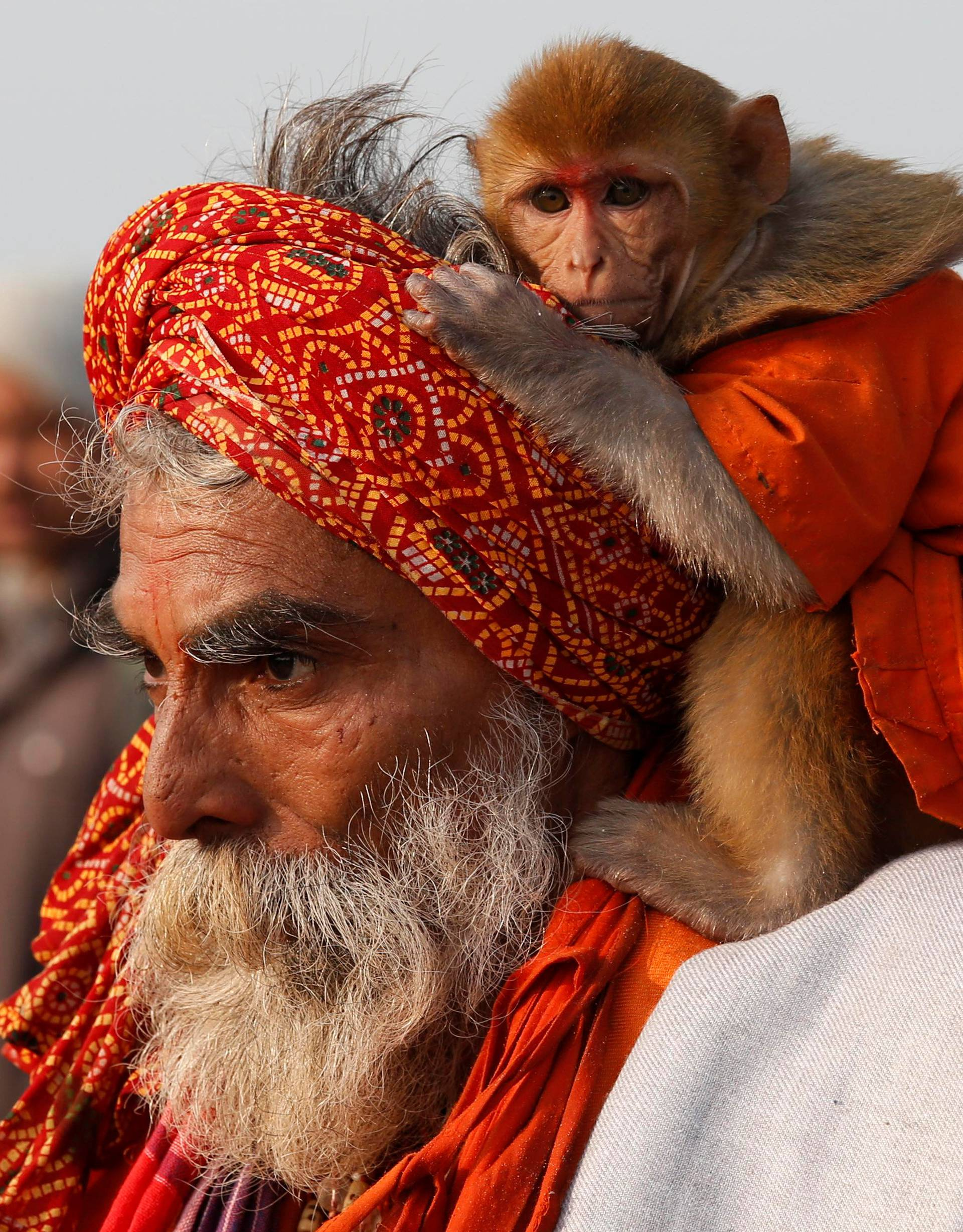 """A Sadhu or a Hindu holy man carrying his pet monkey walks after taking a dip at the confluence of the river Ganges and the Bay of Bengal on the occasion of """"Makar Sankranti"""" festival at Sagar Island"""