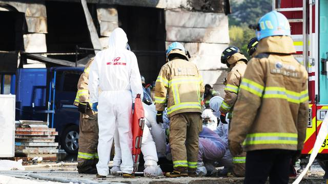 Firefighters and rescue workers check the condition of a survivors rescued from a warehouse which is currently under construction, after it caught fire, in Icheon