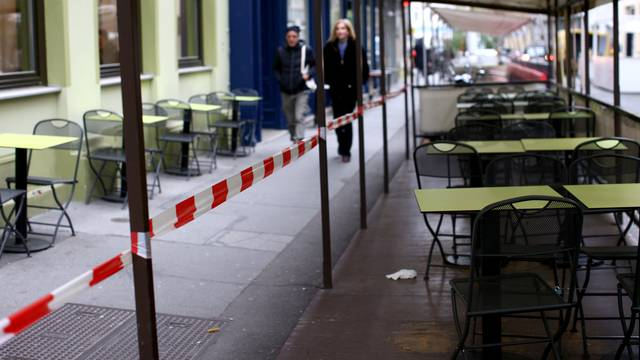 People walk next to abandoned tables of a restaurant during the second lockdown as the coronavirus disease (COVID-19) outbreak continues in Vienna