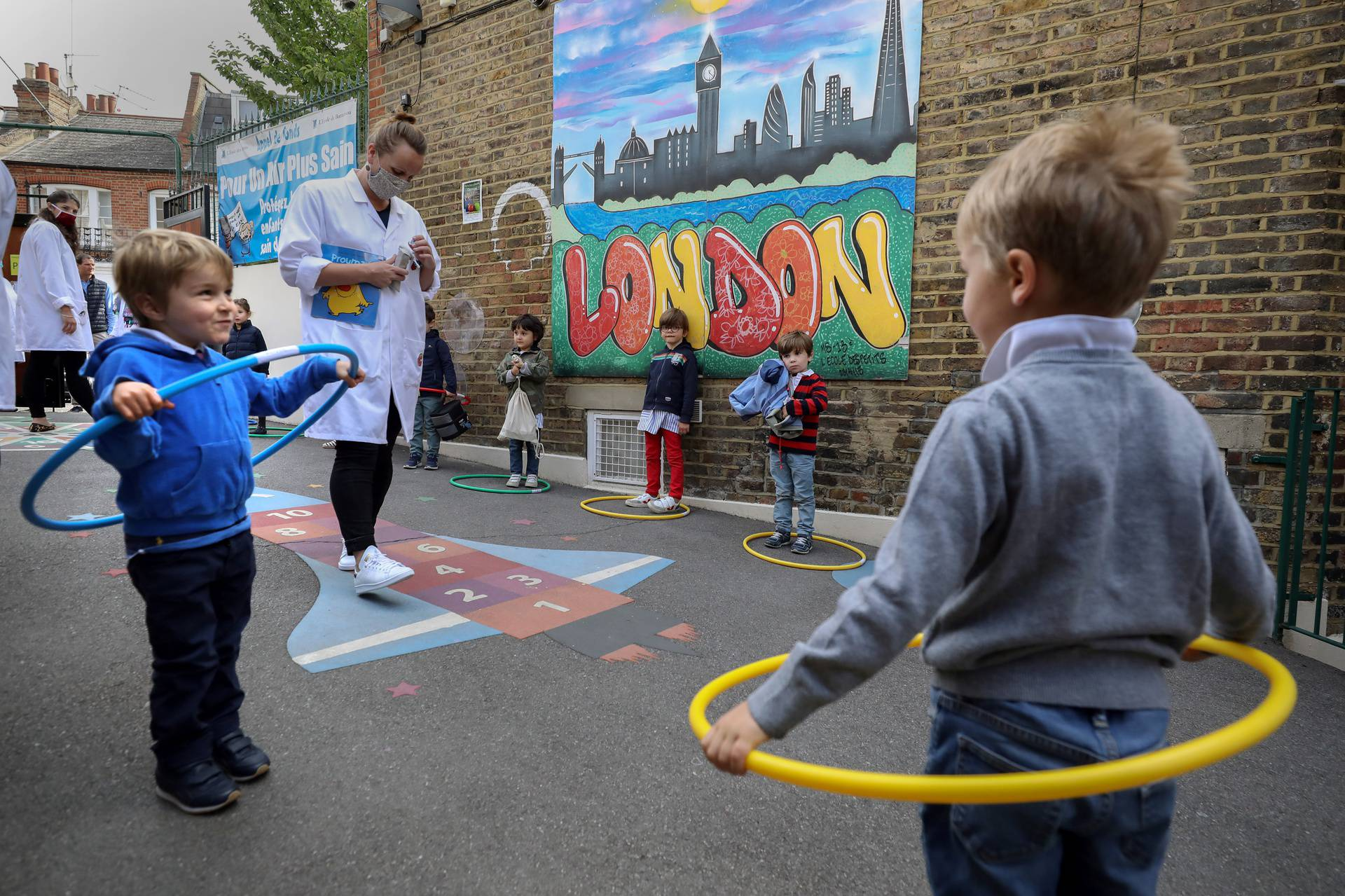 Children use hoops for social distancing at L'Ecole Des Petits school