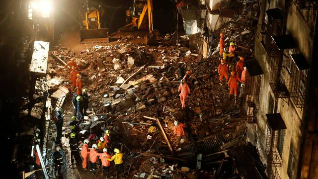 National Disaster Response Force (NDRF) and fire brigade personnel look for survivors trapped in the debris after part of a residential building collapsed following heavy rains in Mumbai