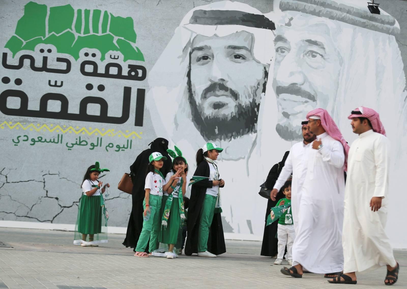 Saudi people walk past a poster depicting Saudi Arabia's King Salman bin Abdulaziz and Crown Prince of Saudi Arabia Mohammad bin Salman during the 89th annual National Day of Saudi Arabia in Riyadh