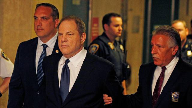 Film producer Harvey Weinstein is led handcuffed by police into his hearing at Manhattan Criminal Court