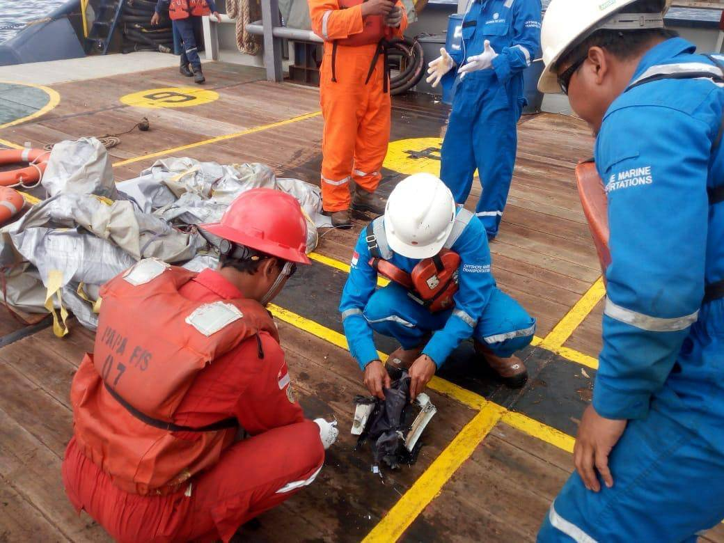 Workers of PT Pertamina examine recovered debris of what is believed to be from the crashed Lion Air flight JT610, onboard Prabu ship owned by PT Pertamina, off the shore of Karawang regency