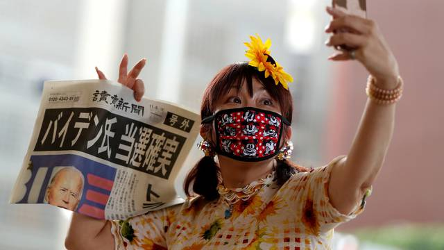A woman takes selfie photo posing with an extra edition of a newspaper reporting that Democratic U.S. presidential nominee Joe Biden is projected to win the 2020 U.S. presidential election, in Tokyo