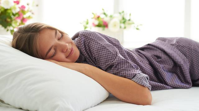Close-up of beautiful woman in satin pajamas sleeping peacefully