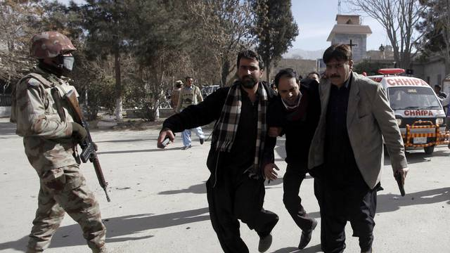 Plain-clothed security officers help an injured man after gunmen attacked the Bethel Memorial Methodist Church in Quetta
