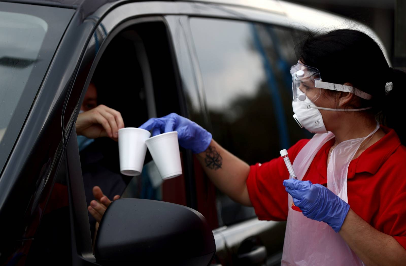 A health worker is seen at a drive-in test center for coronavirus disease (COVID-19) gargle tests at the Ernst Happel Stadium in Vienna