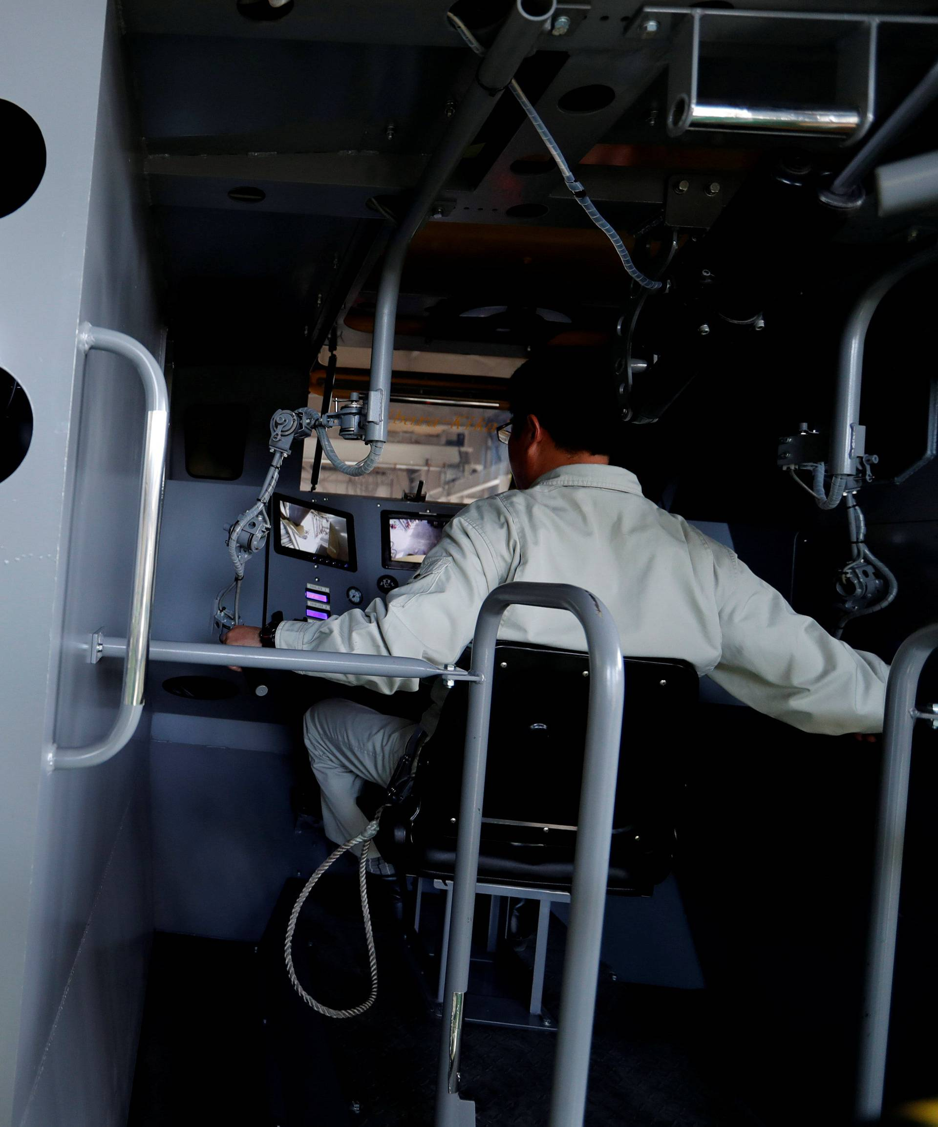 Sakakibara Kikai's engineer Masaaki Nagumo controls the bipedal robot Mononofu from its cockpit during its demonstration at its factory in Shinto Village
