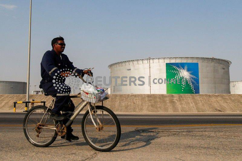 FILE PHOTO: An employee rides a bicycle next to oil tanks at Saudi Aramco oil facility in Abqaiq