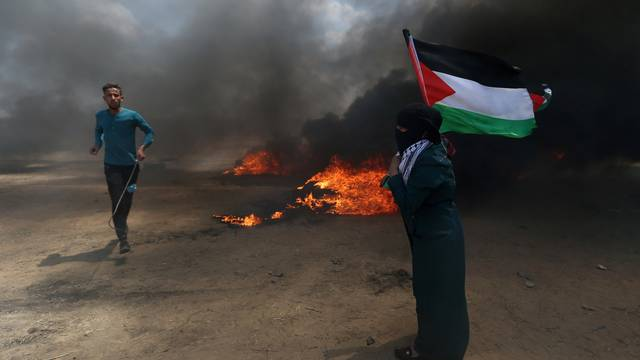 Woman holds a Palestinian flag as a demonstrator runs during a protest against U.S. embassy move to Jerusalem and ahead of the 70th anniversary of Nakba, at the Israel-Gaza border in the southern Gaza Strip