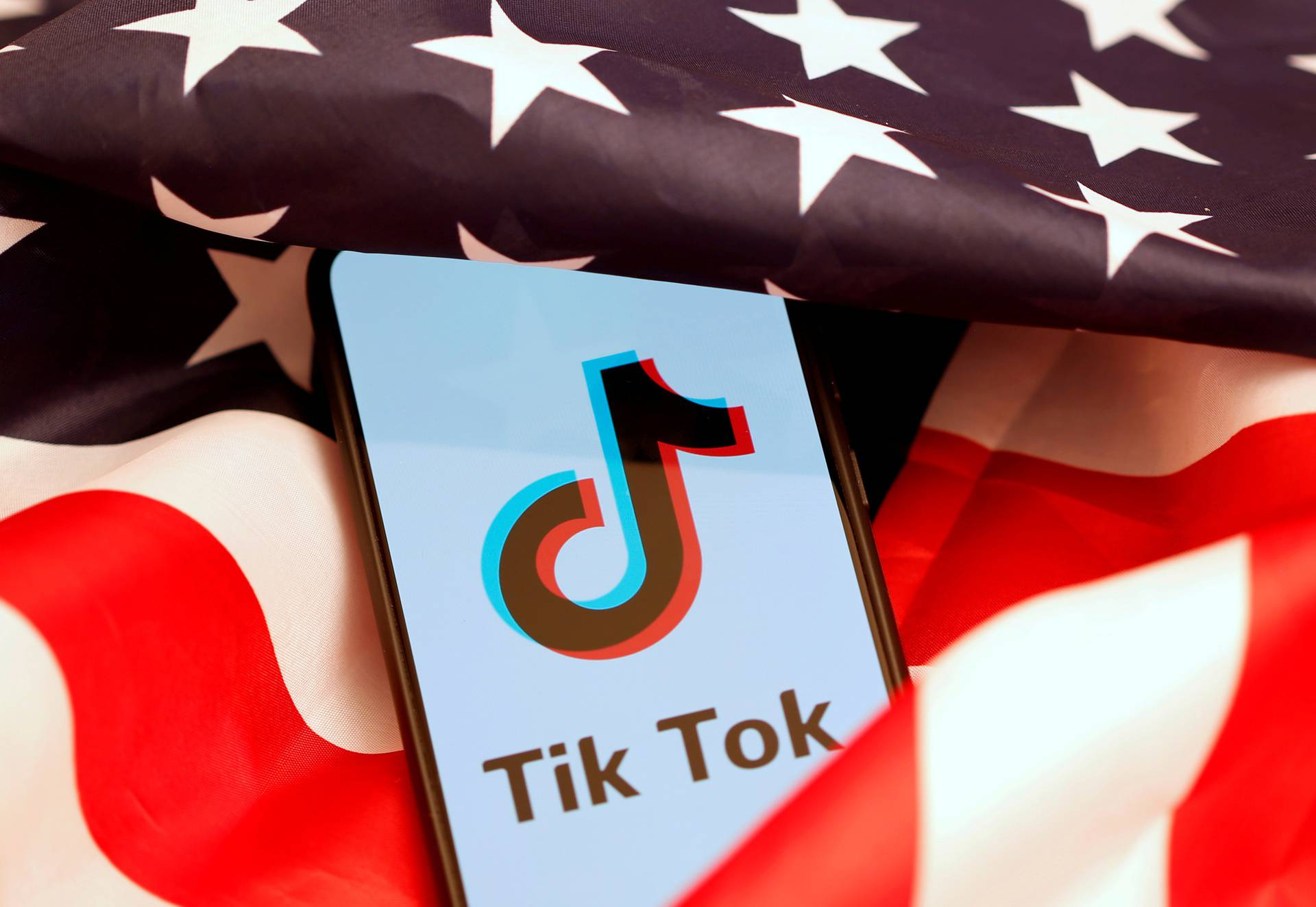 FILE PHOTO: Tik Tok logo is displayed on the smartphone while standing on the U.S. flag in this illustration