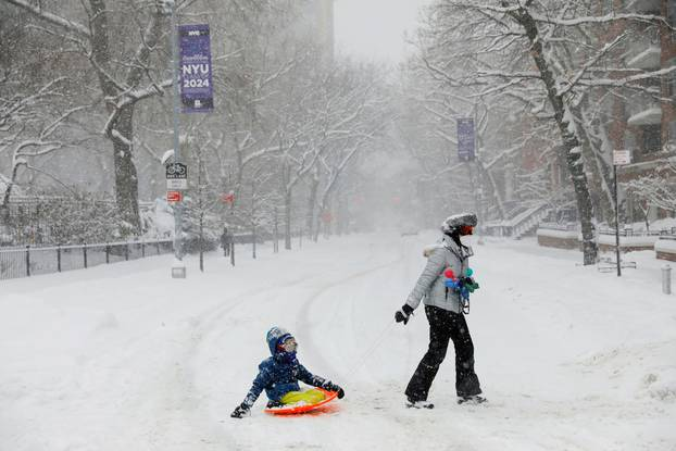 A woman drags a child on a sledge near Washington Square Park during a snow storm in New York