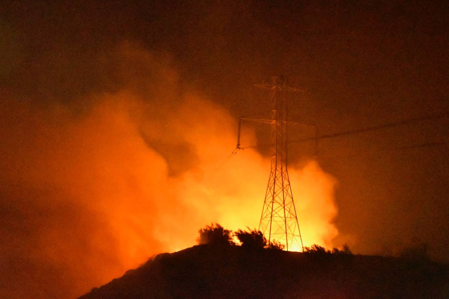 A wind-driven wildfire burns near power lines in Sylmar, California