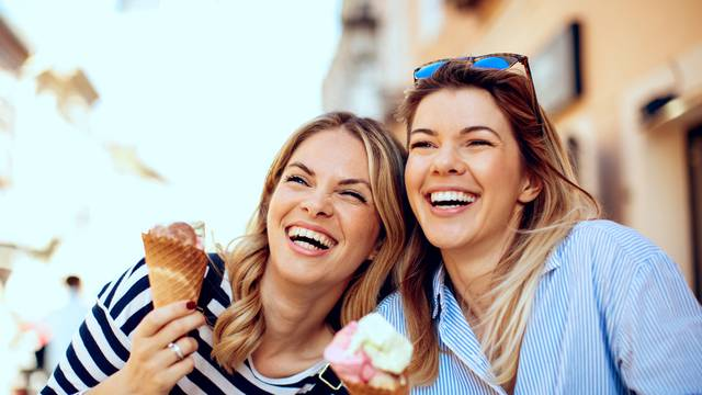 Two young women laughing and holding ice cream in hand