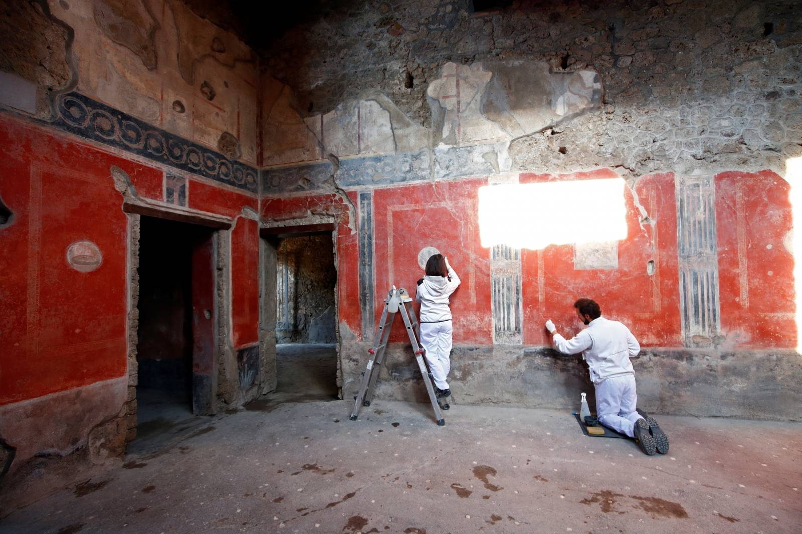 "Archaeologists work on  a fresco in the House of Lovers ""Casa degli Amanti\"