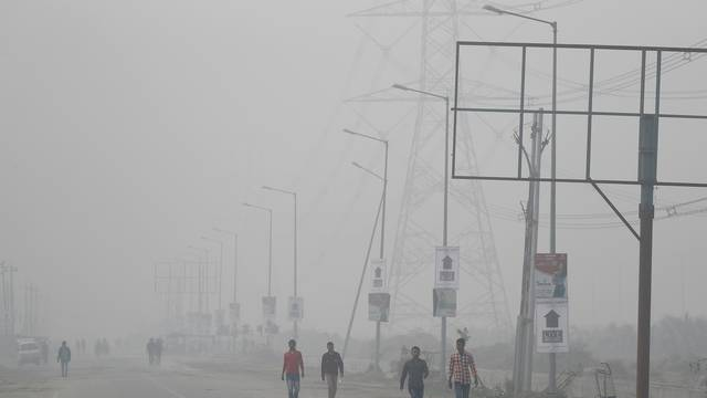 People walk through smog near Delhi