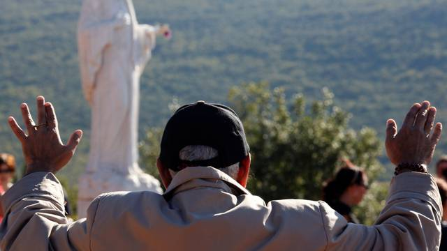 FILE PHOTO: A Catholic pilgrim prays at Podbrdo Hill in Medjugorje