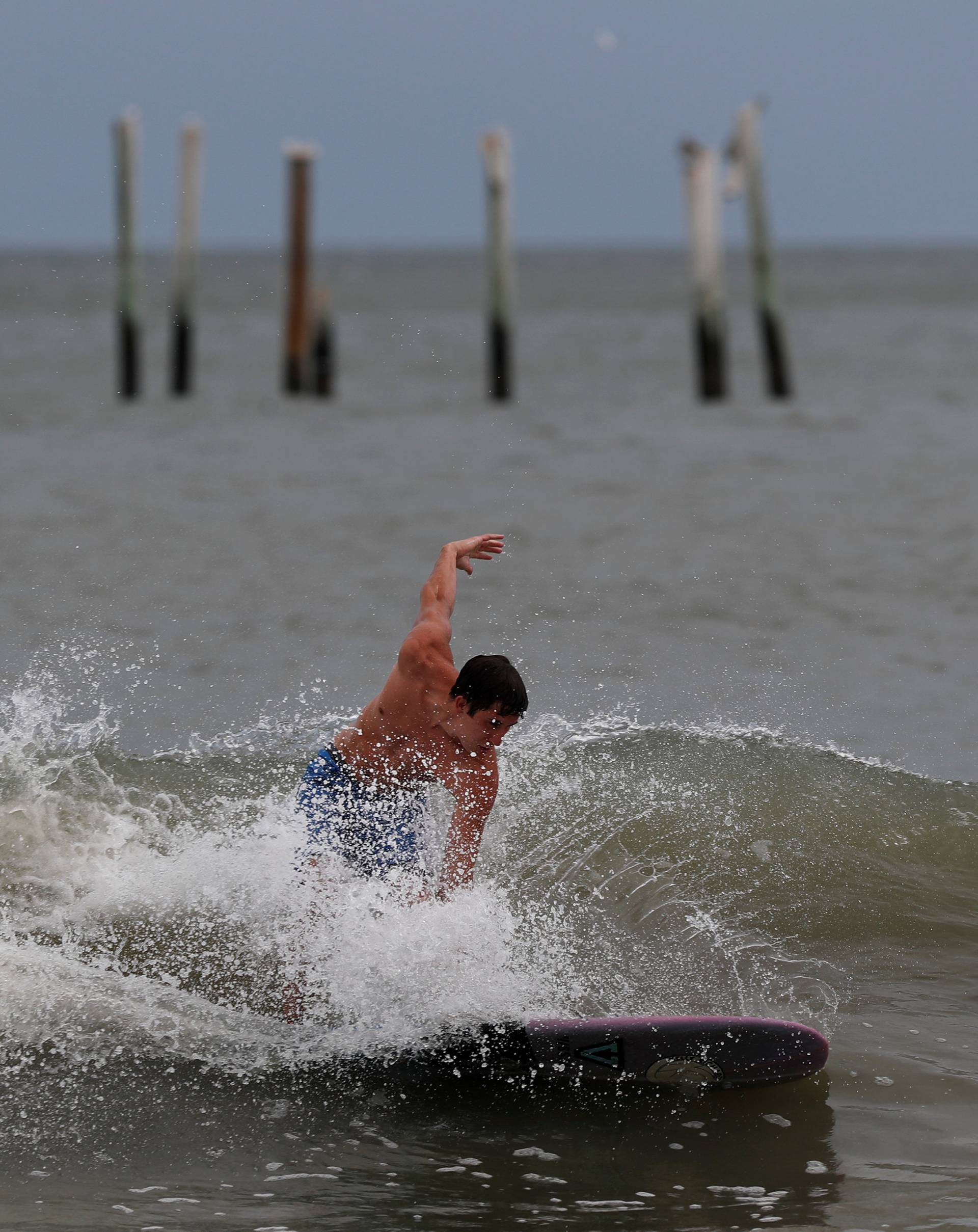 A surfer hits the waves with a backdrop of the Springmaid Pier that was damaged in 2016 by Hurricane Matthew ahead of the arrival of Hurricane Florence in Myrtle Beach