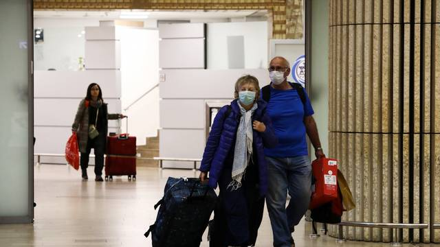 Passengers walk at the arrival area of a terminal at the Ben Gurion airport in Lod